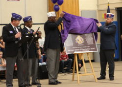Members of the Military Order of the Purple Heart Local Chapter MOPH375 unveil a facsimile of what will eventually be a plaque designating Mission Viejo Elementary School as a Purple Heart School. The school held a ceremony Wednesday evening for earning the designation.