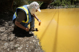 FILE - In this Aug. 6, 2015 file photo, Dan Bender, with the La Plata County Sheriff's Office, takes a water sample from the Animas River near Durango, Colo. after the accidental release of an estimated 3 million gallons of waste from the Gold King Mine by a crew led by the U.S. Environmental Protection Agency. The EPA said Friday, Jan. 13, 2017 that it won't pay claims totaling more than $1.2 billion for economic damages from the spill, saying the law prohibits it.  (Jerry McBride /The Durango Herald via AP, File)