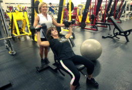 In this June 13, 2016 photograph, Wanda Downs, left, assists Christie Purvis of Tallulah, La., with an incline bench press using dumbbells during their training session at Wyatt's Gym in Vicksburg, Miss. Health clubs and gyms have dropped their rates and initiation fees sharply in the years since the recession, according to the International Health, Racquet & Sportsclub Association. This is partly due to competition from high-volume, low-price chains like Planet Fitness and others that charge under $20 a month. (John Surratt/The Vicksburg Post via AP)