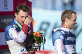 Gold medalist Luca Aerni, left, of Switzerland wipes a tear next to Bronze medalist Mauro Caviezel of Switzerland on the podium during the flower ceremony after the men's combined competition at the 2017 Alpine Skiing World Championships in St. Moritz, Switzerland, Monday, Feb. 13, 2017. (Gian Ehrenzeller/Keystone via AP)