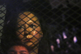 FILE - In this Wednesday, Feb. 8, 2017, file photo, Guadalupe Garcia de Rayos is locked in a van that is stopped in the street by protesters outside the Immigration and Customs Enforcement facility in Phoenix. Advocacy groups said that Immigration and Customs Enforcement officers are rounding up people in large numbers around the country as part of stepped-up enforcement under President Donald Trump. The government said it's simply enforcing the laws and taking dangerous immigrants off the streets. On Wednesday, de Rayos showed up at the ICE building in Phoenix for a scheduled check-in with immigration officers and was swiftly deported to Mexico. (Rob Schumacher/The Arizona Republic via AP, File)