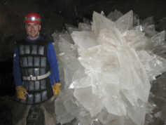In this image provided by Mike Spilde, Mario Corsalini stands near to a gypsum rosette crystal. In a Mexican cave system so beautiful and hot that it is called both Fairyland and hell, scientists have discovered life trapped in crystals that could be 50,000 years old. The bizarre and ancient microbes were found dormant in caves in Naica, Mexico, and were able to exist by living on minerals such as iron and manganese, said Penelope Boston, head of NASA's Astrobiology Institute. (Mike Spilde via AP)