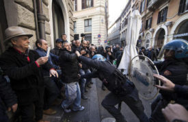 Riot police clash with taxi drivers and street sellers during a demonstration, in Rome, Tuesday, February 21, 2017. A weeklong strike by taxi drivers that has crippled transport in Rome, Milan and Turin is heating up, with cabbies marching through the eternal city to protest legislation they say will favor Uber and other car-hire services.  (Massimo Percossi/ANSA via AP)