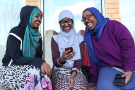 From left, Halimo, Ibrahim, 18, Hallima Ali, 13, and Hafsa Ali, 16, laugh at videos on Tuesday Feb. 21, 2017 at DAVA. Photo by Gabriel Christus/Aurora Sentinel