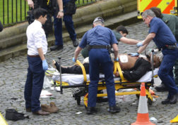 """An attacker is treated by emergency services, as knives lie on the floor, with police looking on at the scene outside the Houses of Parliament London, Wednesday, March 22, 2017.  London police say they are treating a gun and knife incident at Britain's Parliament """"as a terrorist incident until we know otherwise."""" The Metropolitan Police says in a statement that the incident is ongoing. It is urging people to stay away from the area. Officials say a man with a knife attacked a police officer at Parliament and was shot by officers. Nearby, witnesses say a vehicle struck several people on the Westminster Bridge.  (Stefan Rousseau/PA via AP)."""