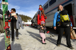 FILE - In this March 15, 2015, file photo, Val Hovland, right, laughs as young Emily Griffin, 4, says all the poles she tries to carry are too heavy, as they head towards Winter Park after riding the Amtrak Winter Park Resort Ski Train at Winter Park, Colo. Behind them are Hovland's husband Ram Sreerangam with young Kavi Hovland, 2, on his shoulders.  Amtrak and the resort announced Wednesday, March 22, 2017, that they are going to keep the train running for the foreseeable future and may possibly expand service. (Helen H. Richardson/The Denver Post via AP)