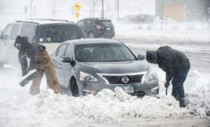 People help dig out a car stuck in a snow drift on Friday, March 24, 2017 in Colorado Springs, Colo., Friday, March 24, 2017.  Blowing snow, low visibility and vehicles sliding off the road initially shut down about 400 miles of roads in southern and eastern Colorado Friday.  (Mark Reis/The Gazette via AP)