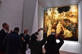 """Visitors take pictures of Leonardo da Vinci's """"Adoration of the Three Wise Men"""", returned to the public of the Uffizi museum after 6 years of study and restoration, in Florence, Italy, Monday, March 27, 2017. Painted in 1481, it is one of the most important works of the early Leonardo. (Maurizio Degl' Innocenti/ANSA via AP)"""