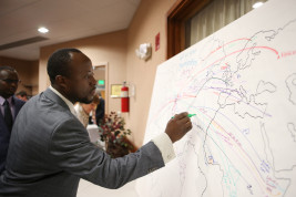 BwaBwa Tchombela draws on a map his immigration story from the Congo on Thursday April 14, 2016 at Aurora Public Library. Photo by Gabriel Christus/Aurora Sentinel