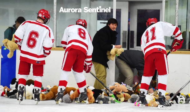 Regis Jesuit players Kale Lone (6), Jack Jordan (8) and Michael Baer (11) help team managers collected the stuffed animals thrown onto the ice during the Raiders' Teddy Bear Toss on Dec. 11, 2015. For the fourth season, the team collected animals thrown by fans after their first goal to be donated to Children's Hospital Colorado. The Raiders topped Resurrection Christian 7-1. (Photo by Courtney Oakes/Aurora Sentinel)