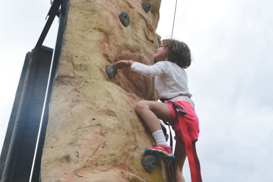 A girl climbs a rock wall during FunFest July 24 at Buckley Air Force Base.