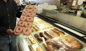 FILE - In this April 26, 2011 file photo, doughnuts are displayed in Chicago. There are a lot fewer trans fats in the nation's food than there were a decade ago, but the Obama administration is moving toward getting rid of them almost entirely. The Food and Drug Administration says Americans still eat about a gram of trans fat every day, and phasing it out could prevent 20,000 heart attacks and 7,000 deaths each year. (AP Photo/M. Spencer Green, File)