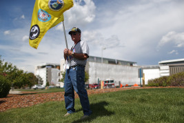 Steve Newton holds a Vietnam Veterans of America Chapter 1071 flag with the unfinished VA hospital in the background during a rally to finish the hospital on Sunday May 31, 2015 at VA Hospital. (Photo by Gabriel Christus/Aurora Sentinel)