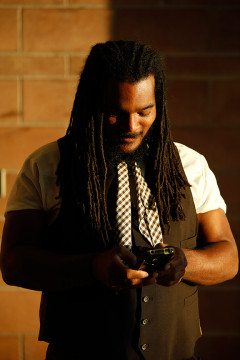 Aurora Poet Laureate, Jovan Mays, checks his phone during a portrait shoot after giving a reading at Cherokee Trail High School April 28, at the Aurora Scholars ceremony.(Photo by Philip B. Poston/Aurora Sentinel)