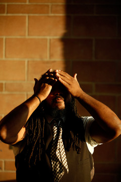 Aurora Poet Laureate, Jovan Mays, gets his hair in order before shooting a portrait at Cherokee Trail High School April 28, after giving a reading to those in attendance for the Aurora Scholars ceremony.(Photo by Philip B. Poston/Aurora Sentinel)