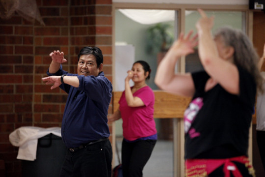 Htoo Hay, left, watches closely for the next step from Wanda Serino-Washington during the Refugee Elder Zumba class at the Aurora Center for Active Adults.