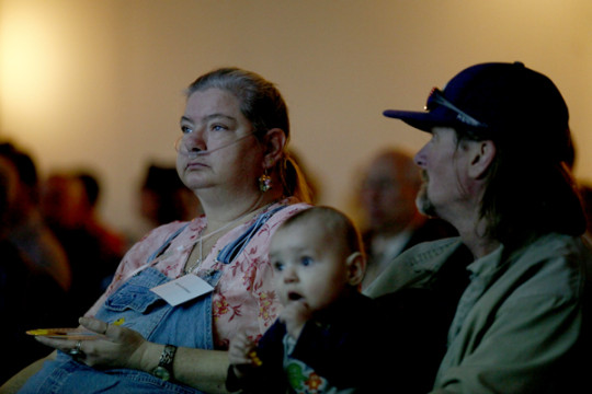 Norma Armistead, watches a video about the Bridges to Care program with Jeff Kirkland and their grandson, RJ, during a graduation ceremony Feb. 4 at the Summit Conference Center. Armistead graduated from the intensive 60 day training program, which is gea
