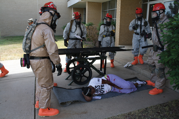 Adrienne Carter awaits aid during a National Guard exercise held at the Community College of Aurora Lowry campus June 9. Carter, a member of the National Guard, was one of 200 participants in a simulation exercise designed to train soldiers for large-scale emergencies.