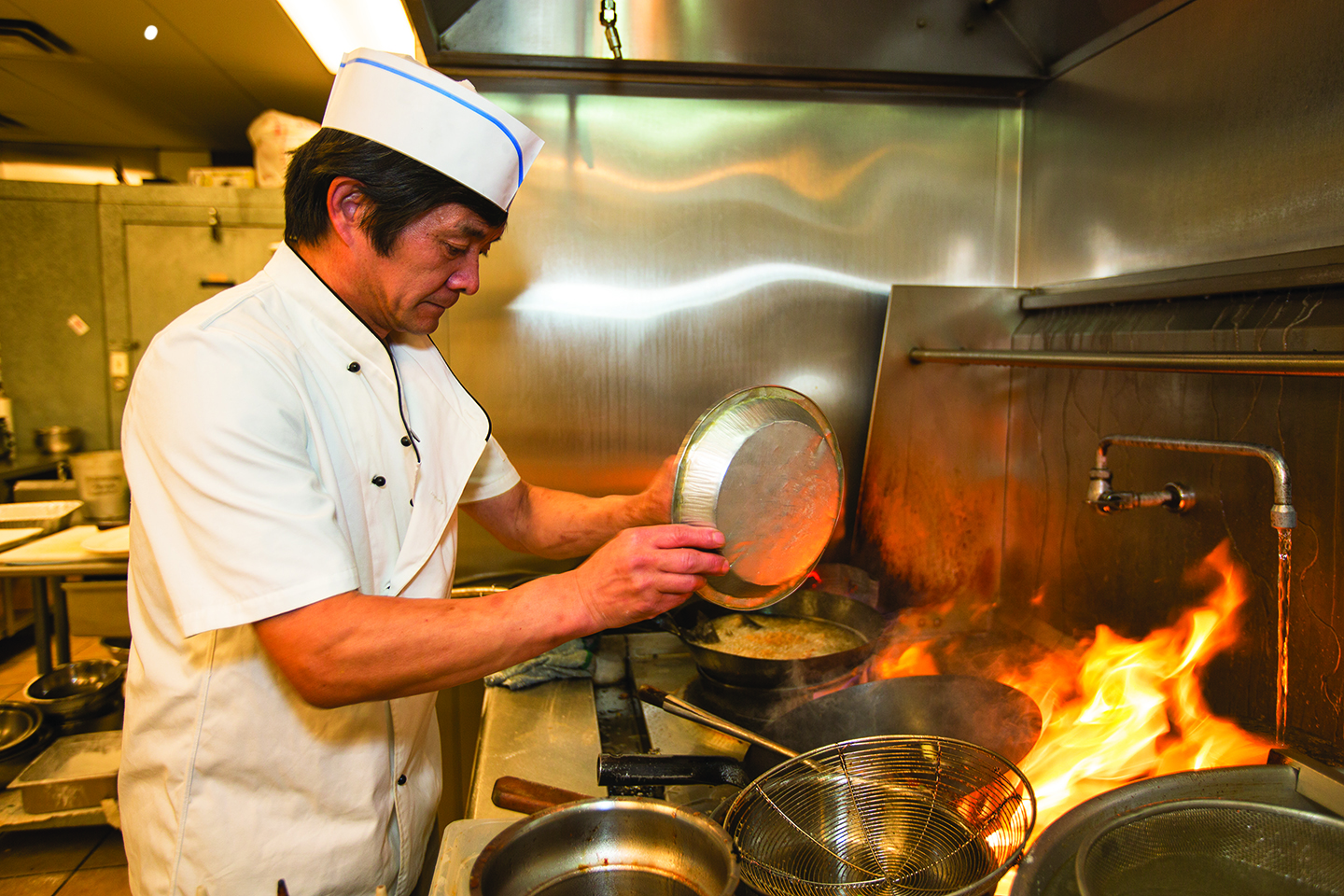 Chef Zeng Qun Liu prepares fried striped bass with tomato sauce at Chef Liu's Authentic Chinese Cuisine in Aurora. The restaurant is featured in Visit Aurora's inaugural Aurora Eats & Drinks poll. (Marla R. Keown/Aurora Sentinel)
