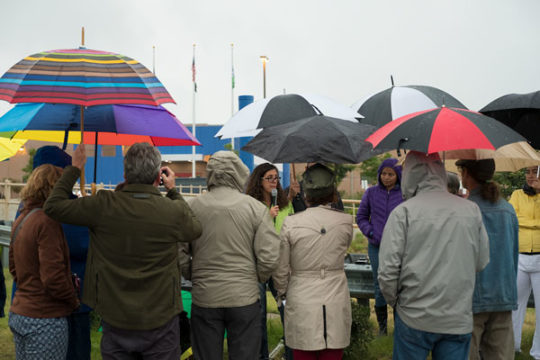 Gabrieala Flora, speaks to a crowd of protestors in the rain, Aug. 7, outside the GEO Detention Center. The protest and vigil was a kick-off of a month of actions across the country in partnership with the Detention Watch Network and the Interfaith Immigr