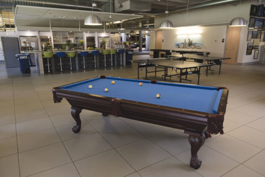 The break room in the new American Finance office features a pool table, two shuffleboard tables, ping pong, arcade-style basketball and a fully stocked refrigerator, compliments of the founders Gabie and Damian Maldonado. The new larger offices will allo
