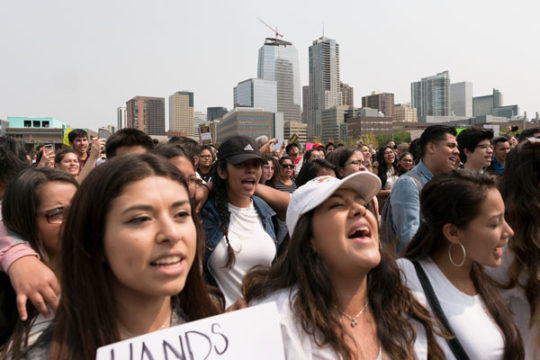 Protestors chant in unison, arms around one another, Sept. 5 in the field outside of the Tivoli at Auraria Campus in downtown Denver. The protest is in response to the announcement made by Jeff Sessions that a policy from the Obamam Administration, protec
