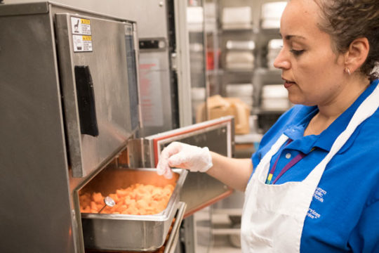 Lesli Argueta, who is the kitchen manager at Peoria Elementary School, checks the temperature of sweet potatoes, which, along with carrots, are to be incorporated into macaroni and cheese, guaranteeing good nutritional value in the students lunches.