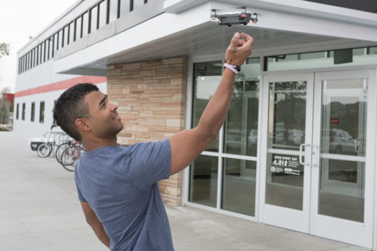 Owen Brown, drone flight instructor at Minecraft makerspace, tries to land his drone in his hand using a special gesture feature. Brown has been offering private drone classes for two months and hopes to soon be incorporating larger classes on drone flyin