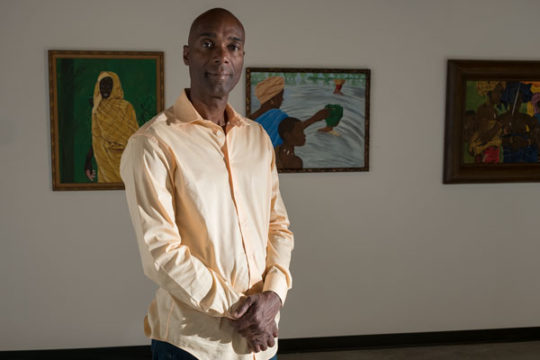Ndume Olatushani stands for a portrait in front of a few of his pieces of art work, Sept. 12 at Zeel Gallery in Stanley Marketplace. Ndume was wrongly imprisoned for 28 years, 20 of which were spent on death row and the other eight spent in general popula