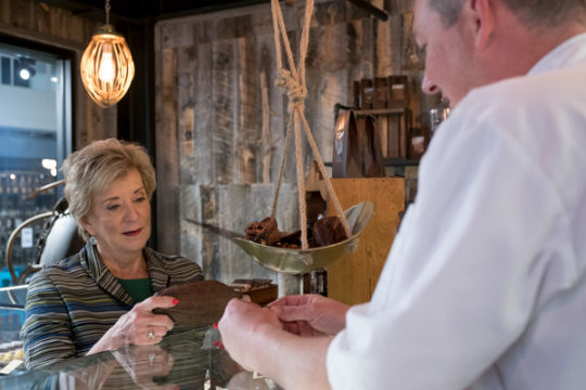 Administrator of the Small Business Administration, Linda McMahon, examines a cocoa pod with co-owner David Lewis at his French patisserie, Sept. 28 at the Stanley Marketplace.