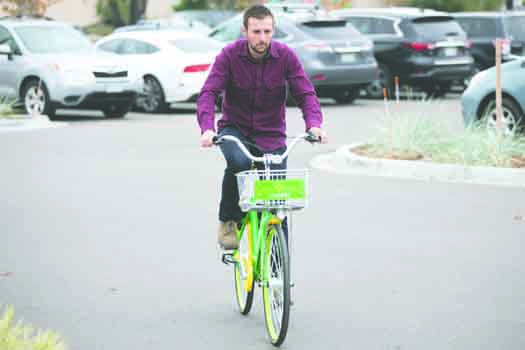 Brenden Paradeis rides a new Lime Bike, Oct 6 at the Stanley Marketplace. The new bike-share service has these lime green and yellow bicycles parked throughout the city, available for use for $1.00 per 30 minutes.