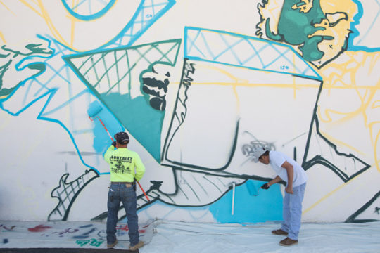 Day laborers assist in painting a mural on the north side of the day labor building near the corner of Dayton and Colfax, Oct. 4. The mural, designed by Bimmer Torres, is focused on illustrating the community of day laborers. Photo by Philip B. Poston/Au