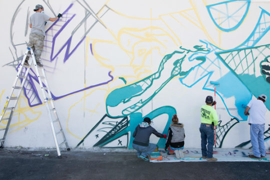 Bimmer Torres, left, with the help of several day laborers, paint a mural Oct. 4, on the north side of the day labor building near the corner of Dayton and Colfax.The mural, designed by Bimmer Torres, is focused on illustrating the community of day labore