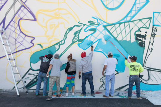 Bimmer Torres, second from left,  with the help of several day laborers, paint a mural Oct. 4, on the north side of the day labor building near the corner of Dayton and Colfax.The mural, designed by Bimmer Torres, is focused on illustrating the community