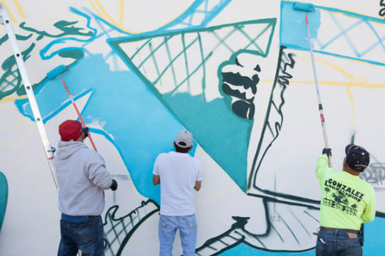 Day laborers assist in painting a mural on the north side of the day labor building near the corner of Dayton and Colfax, Oct. 4. The mural, designed by Bimmer Torres, is focused on illustrating the community of day laborers. 