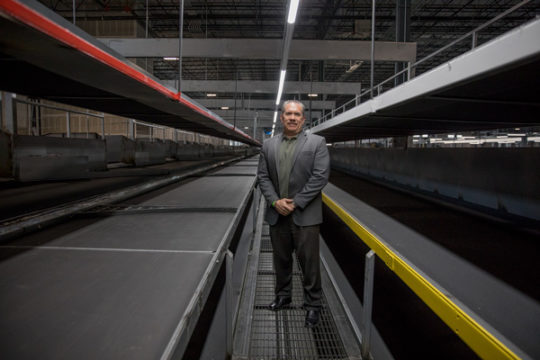 UPS West Region Project Engineering Manager, Robert Gonzalez, stands for a portrait in between lines and stacks of conveyer belts, each with a specific destination in the 360,000 square foot warehouse, which opened Nov. 1.