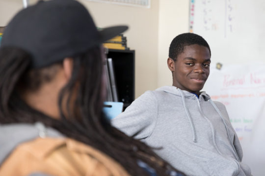 Daniel Mateso, right, talks with Jovan Mays in Kati Van Sicklen's classroom, Nov 7 at Aurora Central High School. Daniel is one of the students contributing to the new A Story website, which provides an outlet for students to tell personal narratives in a