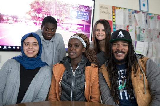 From left, students Haneen Aljamal, Daniel Mateso, Solange Bizoza, their teacher, Kati Van Sicklen and former Aurora Poet Laureate, Jovan Mays, all worked together on the launch of the new A Story website, which is produced at Aurora Central High School..