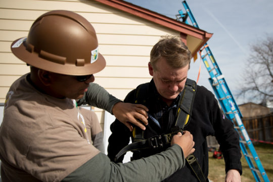 Sen. Michael Bennet , D-CO, right, has his harness adjusted before going onto the roof to install solar panels, with workers and volunteers of GRID Alternatives Colorado, Nov. 10 in Aurora , CO. Photo by Philip B. Poston/Aurora Sentinel