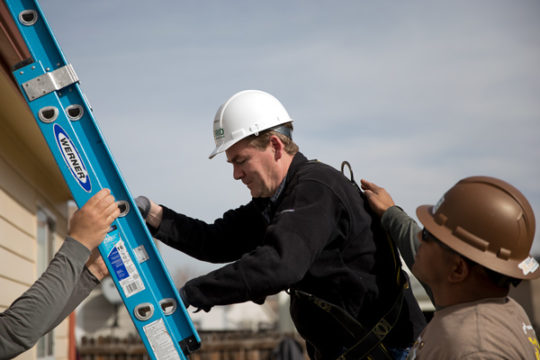 Sen Michael Bennet, D-CO, ascends a ladder up to the roof to help install solar panels with workers and volunteers of GRID Alternatives Colorado, Nov. 10 in Aurora , CO. Photo by Philip B. Poston/Aurora Sentinel