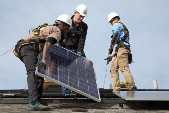 Sen. Michael Bennet, center, lays downs a solar panel with the projects Solar Installation Supervisor, Mario Braxton, on the roof of the home of the Ortiz-Galvan's. The solar panels are expected to save the family $500 annually on electricity.Photo by Ph