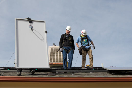 Sen. Michael Bennet, D-CO, with the help of Keith Rohman, is familiarized with the grid structure before installing a solar panel, held by Mario Braxton, left, on the roof of the Ortiz-Galvan home, Nov. 10 in Aurora, CO. Photo by Philip B. Poston/Aurora