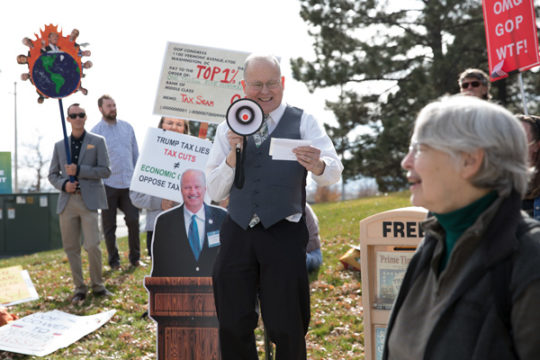 Playing the role of Wilbur J. Moneybags, Kenneth Nova sarcastically describes why he loves the new Republican tax plan, Nov. 14 outside of Mike Coffman's office. Over 60 protestors gathered to show their opposition of the new plan. Photo by Philip B. Po
