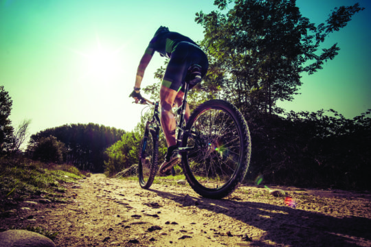 Man riding on a dirty road on a mountain bike
