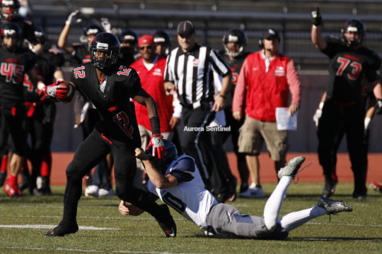 Eaglecrest wide receiver, Victor Garnes, 12, drags Columbine defensive back, Logan DeArment, 10, stretching out the play for extra yards before eventually being brought down during the class 5A football semifinal contest, Nov. 25 at Legacy Stadium. Eaglec