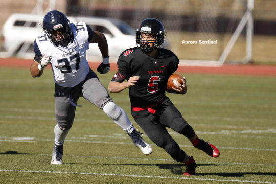 Eaglecrest quarterback, Jalen Mergerson, 6, looks upfield as he escapes from Columbine defensiveman Corbin Curry, for a run resulting in a first down, during the class 5A football semifinal contest, Nov. 25 at Legacy Stadium. Eaglecrest defeated Columbine