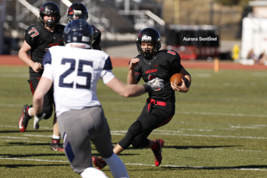 Eaglecrest quarterback, Jalen Mergerson, 6, looks upfield as he makes a move to avoid Columbine linebacker, Ted Mullin, 25, during the class 5A football semifinal contest, Nov. 25 at Legacy Stadium. Eaglecrest defeated Columbine in double overtime 32-31 a