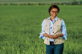 Aurora State Sen. Rhonda Fields outstanding in a field on a constituent's farm. Photo appeared on FarmFlavor.com