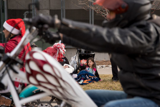 Amanda Ortiz-Martinez is seen waving to motorcyclists as they enter the Children's Hospital Colorado campus to deliver toys to the patients Dec. 3, during the 32nd Annual Children's Hospital Colorado  Toy Run. Thousands of motorcyclists met at Aurora Spor