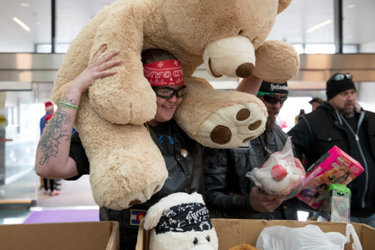 Alissa Davis heaves a giant teddy bear from her shoulders into a donation bin in the atrium of the children's hospital Dec. 3 during the 32nd Annual Children's Hospital Colorado Toy Run. This is Alissa's second year participating in the event, where thous